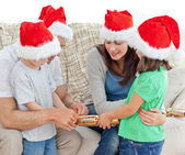 Family opening crackers together on the sofa — Stock Photo