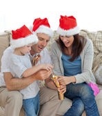 Happy parents with thir opening crackers together — Stock Photo