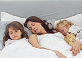 Adorable children sleeping with their mother on her bed — Stock Photo