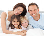 Lovely family sitting together on the bed — Foto de Stock