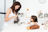 Pretty mom pouring coffee while her children having breakfast — Stock Photo