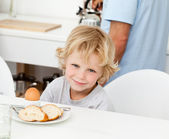 Little boy eating boiled egg and bread at breakfast — Stockfoto