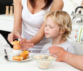Attentive mother breaking a boiled egg for her son during breakf — Stockfoto