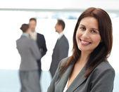 かなりビジネスウーマンが働いている間彼女のチームの前でポーズ — ストック写真