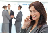 彼女のチームが働いている間電話で幸せな女性実業家 — ストック写真