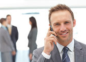 Happy businessman on the phone while his team working — Stock Photo