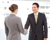 Cheerful businessman and businesswoman concluding a deal — Stock Photo