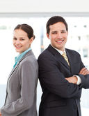 Happy businessman and businesswoman posing back to back — Stock Photo