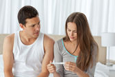 Worried couple looking at a pregnancy test sitting on their bed — Stock Photo