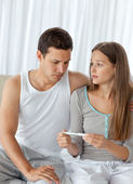Man looking at a pregnancy test with his girlfriend — Stock Photo