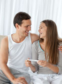 Happy couple with a pregnancy test sitting on the bed — Stock Photo