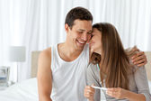 Cheerful couple with a pregnancy test in the bedroom — Stock Photo