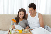 Young woman having breakfast on the bed with her boyfriend — Stock Photo