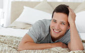 Joyful man lying on th edge of his bed at home — Stock Photo