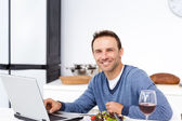 Happy man looking at his laptop while eating a salad — Stock Photo
