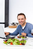 Cheerful man working on his laptop while having lunch — Stock Photo