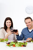 Lovely couple drinking red wine while having lunch — Stock Photo
