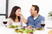 Attentive man giving a tomato to his girlfriend while having lu — Stock Photo