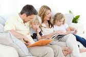 Family reading a book on their sofa — Stock Photo
