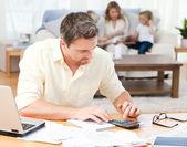 Człowiek obliczania swoje rachunki, a jego rodzina na kanapie — Zdjęcie stockowe