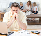 Man calculating his bills while his family are on the sofa — Stock Photo