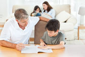 Father helping her son with his homework — Stock Photo