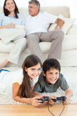 Children playing videogames while parents are talking — Stock Photo