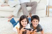 Bambini che giocano videogames mentre i genitori stanno parlando — Foto Stock