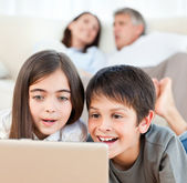 Lovely children watching a movie on their laptop at home — Stock Photo