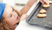 Little girl stealing cookies — Stock Photo