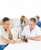 Men playing chess while their wifes are talking — Stock Photo