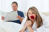 Happy woman smelling her rose while her husband is reading a new — Stock Photo