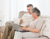 Retired lovers looking at their laptop — Stock Photo