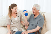 Lovely nurse helping her patient to do exercises — Stock Photo