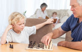 Young boy playing chess with his grandfather — Foto Stock