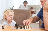 Young boy playing chess with his grandfather — Стоковое фото