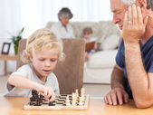 Young boy playing chess with his grandfather — Stock Photo