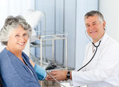 A senior doctor taking the blood pressure of his patient — Stock Photo