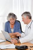 Um médico sênior com seu paciente olhando para o laptop — Foto Stock