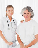 Senior with her nurse looking at the camera — Stock Photo