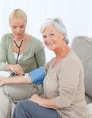 Lovely doctor taking the blood pressure of her patient — Stock Photo
