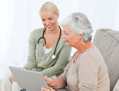 Senior with her doctor working on the laptop — Stock Photo
