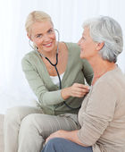 Nurse taking the heartbreat of her patient at home — Stock Photo