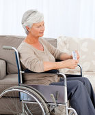 Senior in wheelchair with pills — Stock Photo