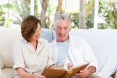 Personas mayores en su álbum de fotos en casa — Foto de Stock