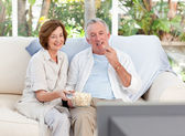 Seniors watching tv at home — Stock Photo