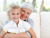 Lovely little girl with her grandmother looking at the camera — Foto Stock