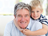 Little boy with his grandfather looking at the camera — Stockfoto