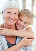 Lovely little girl with her grandmother looking at the camera — Foto de Stock