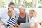 Adorable family looking at their laptop — Stock Photo